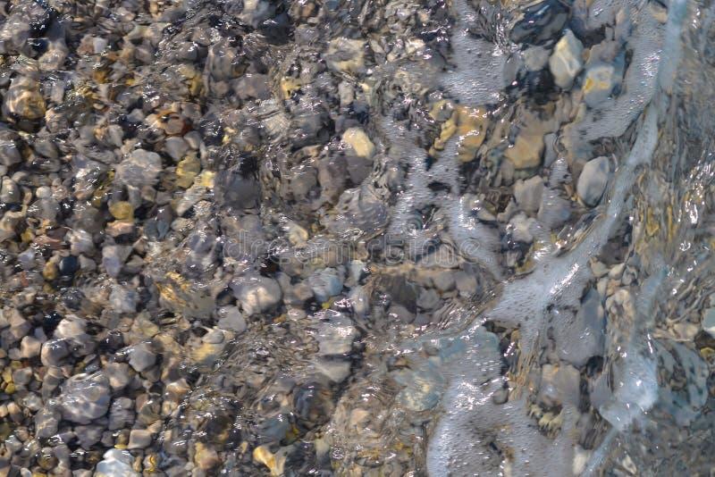 海滩小卵石和软的泡沫波浪;海石头背景 免版税库存图片