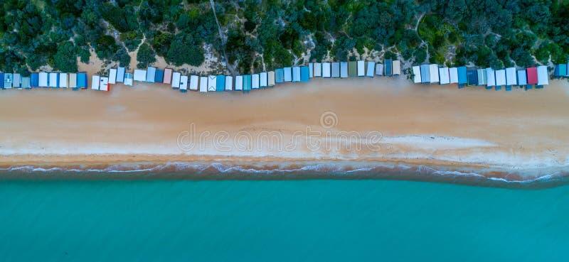 海滩小屋和美丽的绿松石水长的行  免版税库存图片