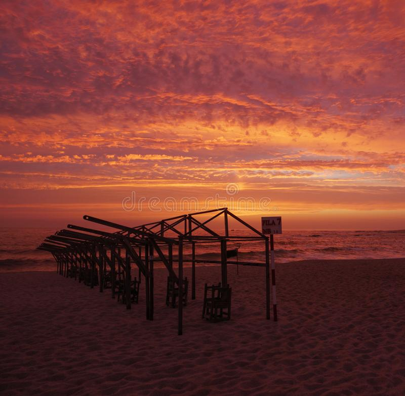 海滩小屋框架现出轮廓反对生动的红色日落天空 图库摄影