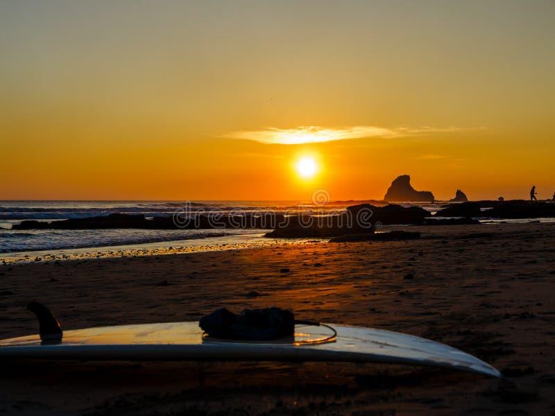 海滩岩石日落冲浪板 免版税库存照片