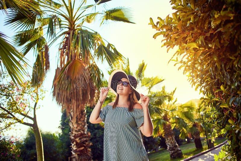 海滩帽子的年轻美女走在热带棕榈树下的在好日子在博德鲁姆,土耳其 假期户外海景 免版税库存照片