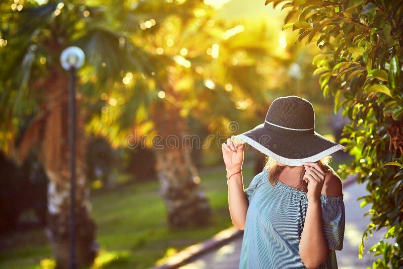 海滩帽子的年轻美女走在热带棕榈树下的在好日子在博德鲁姆,土耳其 假期户外海景 免版税库存图片