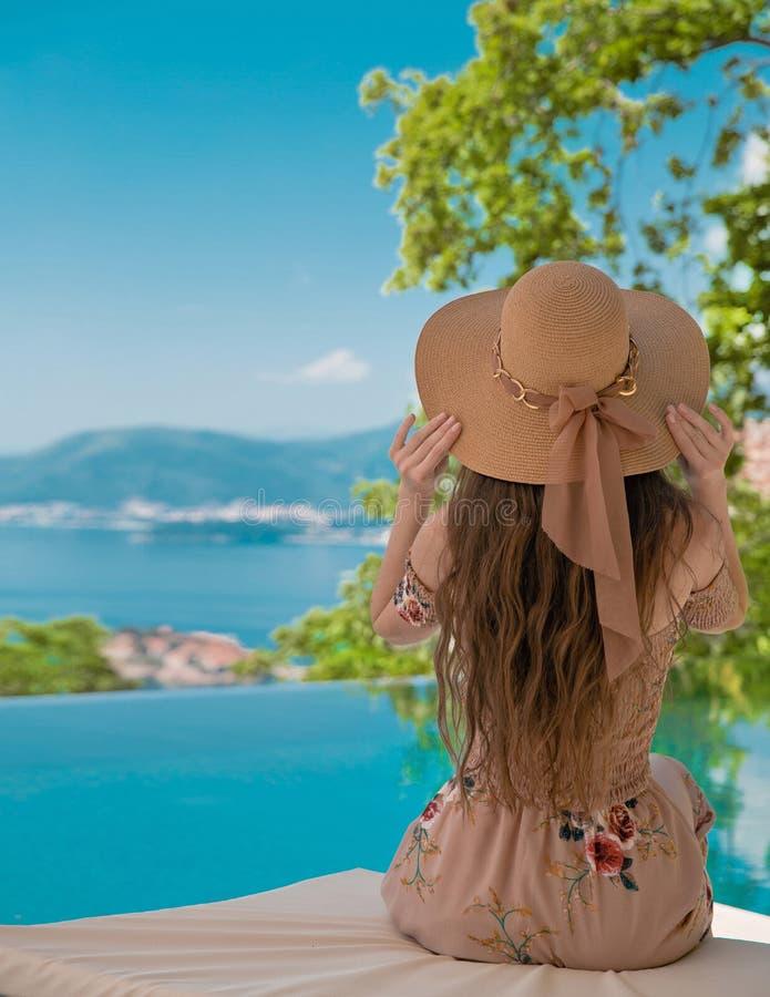 海滩帽子的美丽的时尚妇女享受海视图的由swimmi 免版税库存照片