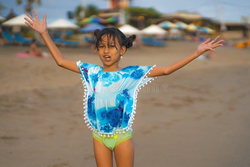 海滩年轻美好和愉快的亚洲儿童女孩8或9岁生活方式画象与逗人喜爱双重小圆面包头发使用的 图库摄影