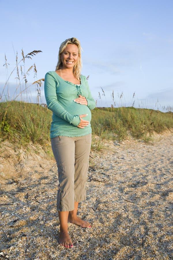 海滩愉快的怀孕的常设妇女年轻人 免版税图库摄影