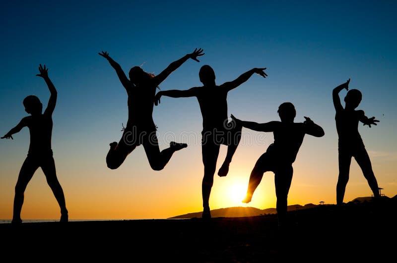 海滩愉快的跳的孩子剪影 库存图片