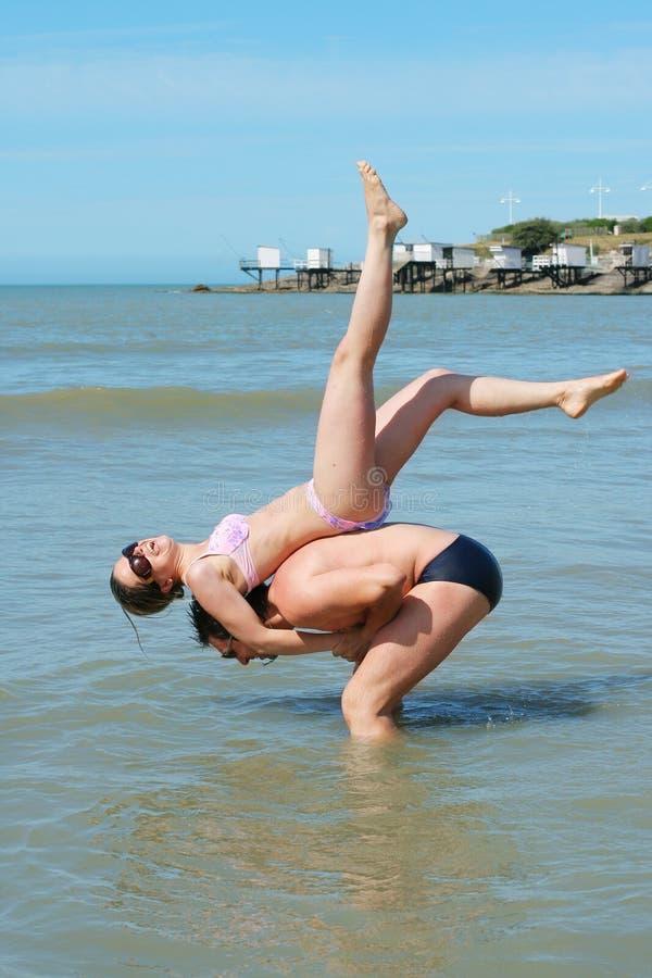 海滩有夫妇的乐趣年轻人 免版税图库摄影