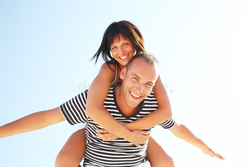 海滩有夫妇的乐趣微笑的年轻人 免版税库存照片