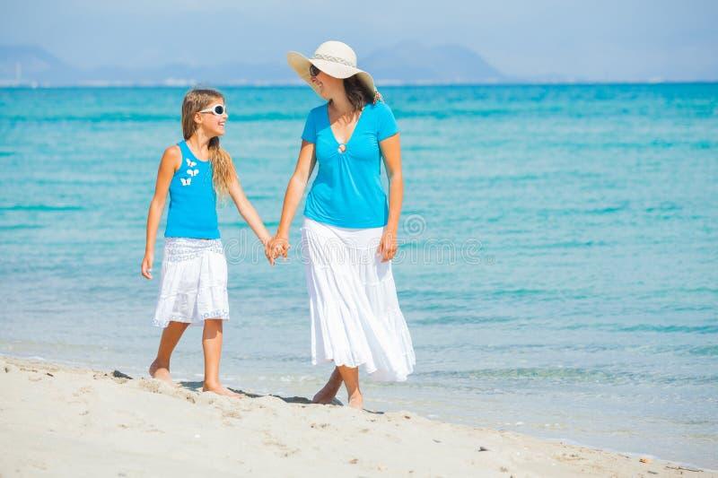 海滩有女儿的乐趣她的母亲 免版税库存照片