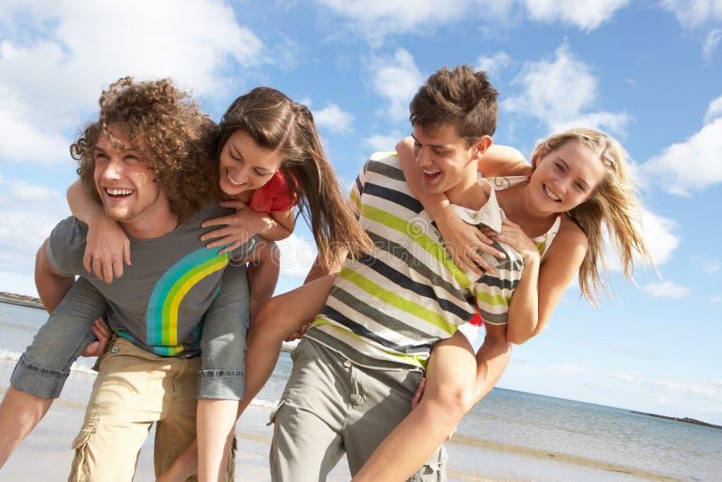海滩有朋友的乐趣夏天年轻人 免版税图库摄影