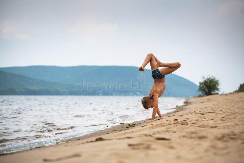 海滩步行的男孩在他的手上 夏日,河岸 免版税库存照片