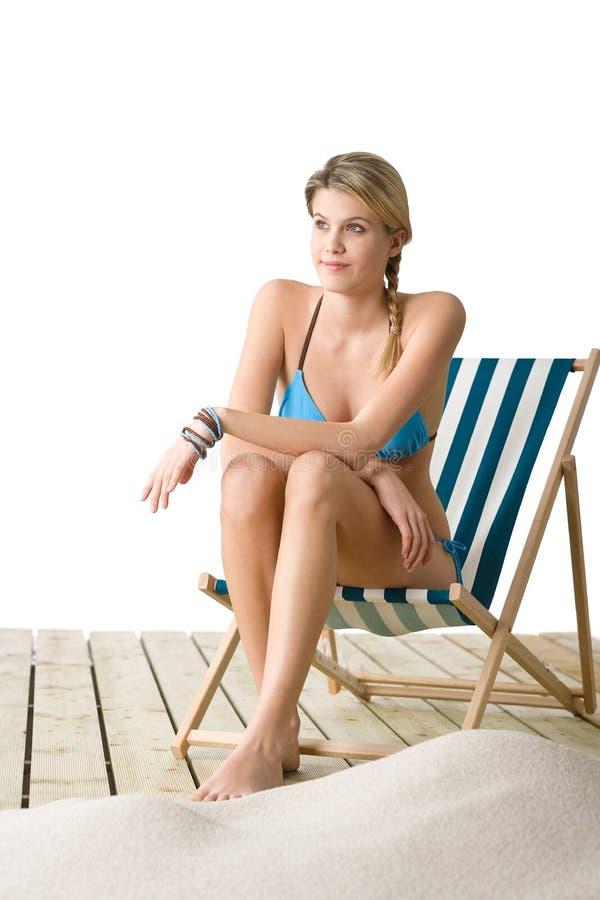 海滩比基尼泳装椅子甲板坐的妇女 免版税图库摄影
