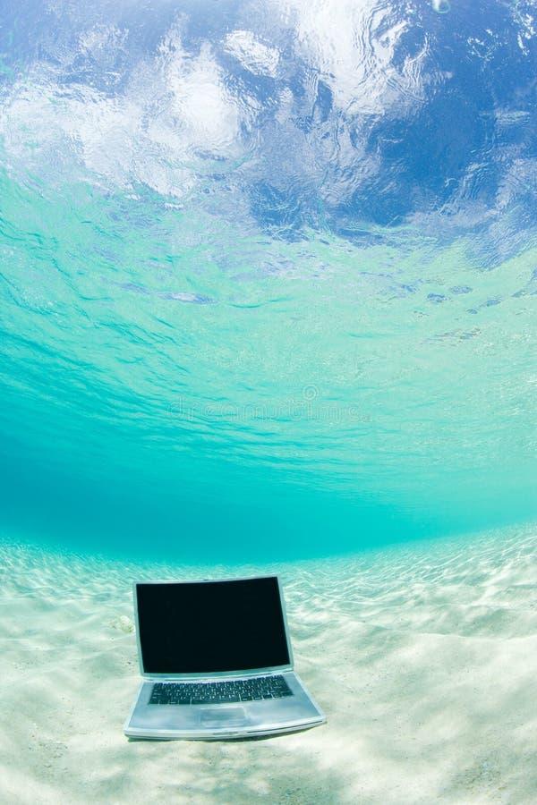 海滩水下计算机的笔记本 图库摄影