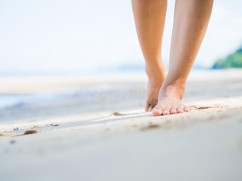 海滩沙子走的妇女 女性脚特写镜头细节  提高概念 免版税库存照片