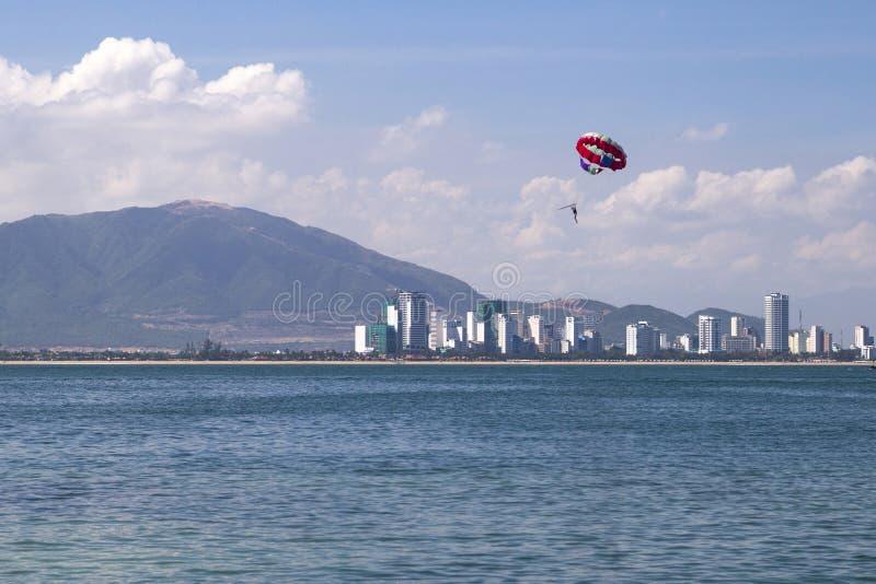 海滩活动:帆伞运动,高速小船拉扯p的一个女孩 免版税库存照片
