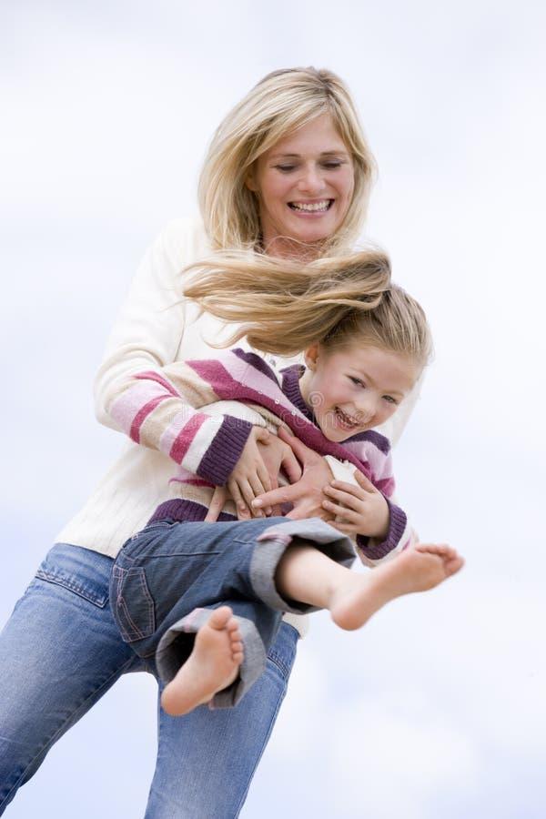 海滩演奏微笑的女儿母亲 免版税库存照片