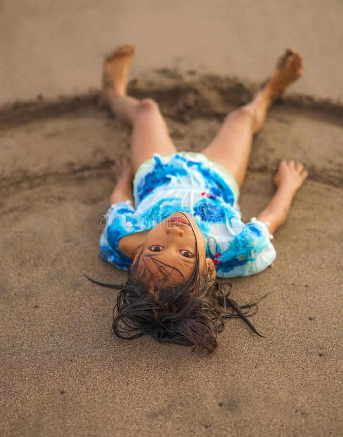 海滩演奏说谎的年轻美好和愉快的亚裔美国人混杂的种族儿童女孩7或8岁生活方式画象  免版税库存照片
