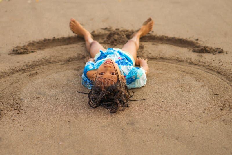 海滩演奏说谎的年轻美好和愉快的亚裔美国人混杂的种族儿童女孩7或8岁生活方式画象  免版税库存图片