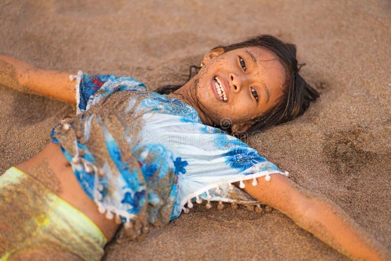 海滩演奏说谎的年轻美好和愉快的亚裔美国人混杂的种族儿童女孩7或8岁生活方式画象  图库摄影