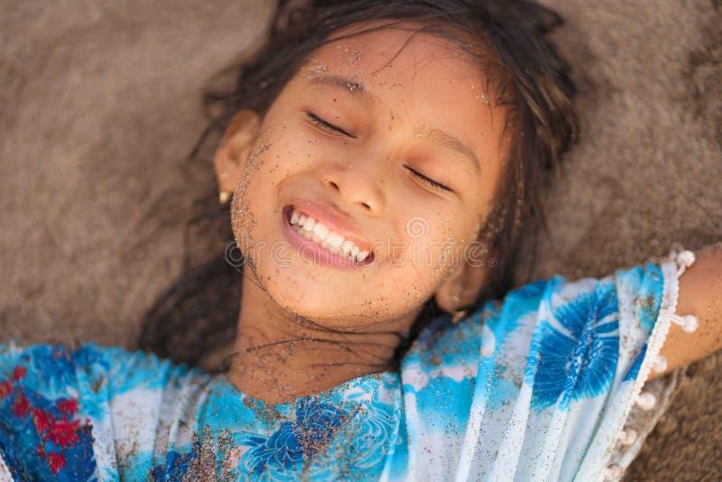 海滩演奏说谎的年轻美好和愉快的亚裔美国人混杂的种族儿童女孩7或8岁生活方式画象  库存照片
