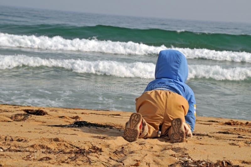 海滩爬行的孩子海运 免版税图库摄影