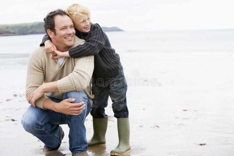 海滩父亲微笑的儿子 免版税库存照片