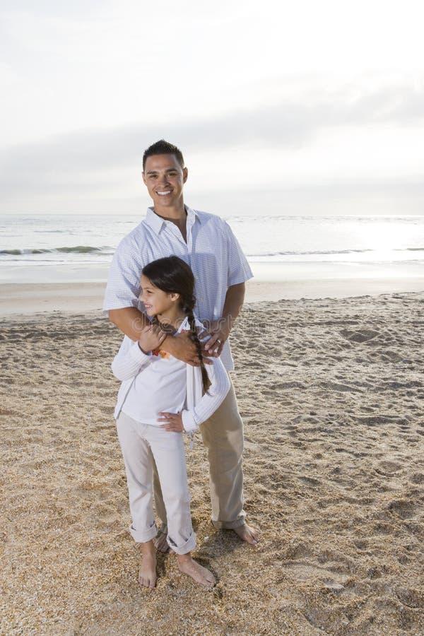 海滩爸爸一起突出女孩的讲西班牙语&# 库存照片