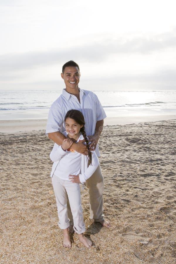 海滩爸爸一起突出女孩的讲西班牙语&# 免版税图库摄影