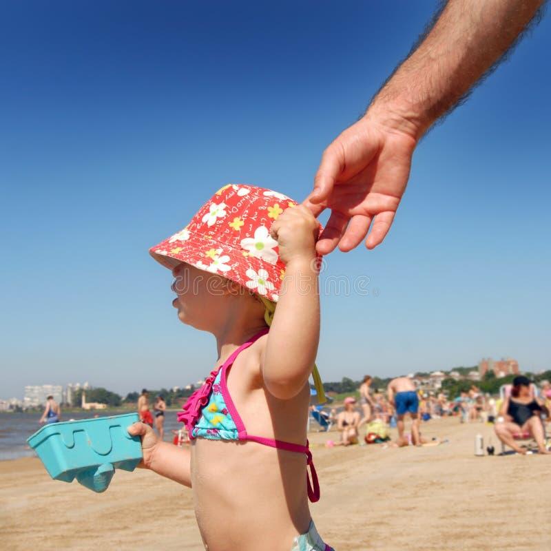 海滩生女孩递她藏品litlle 免版税库存照片