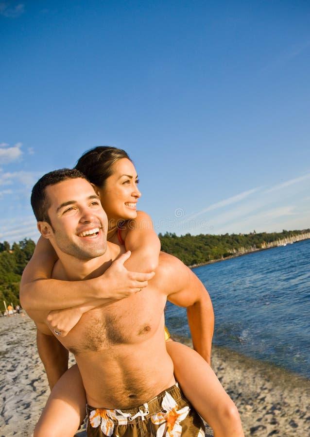 海滩男朋友运载的女朋友 库存图片