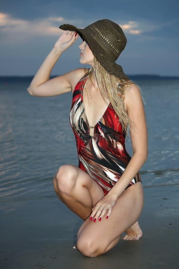 海滩白肤金发的坐的妇女 库存照片