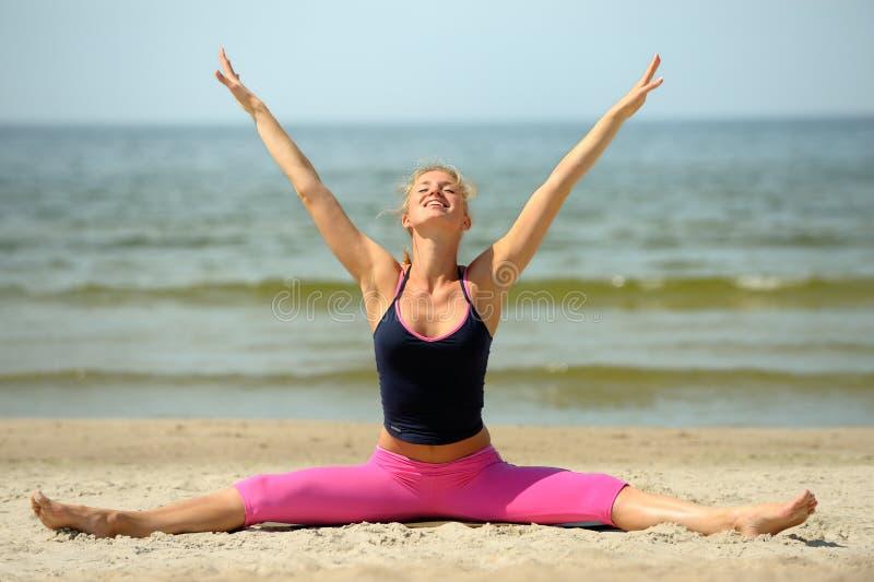 海滩白肤金发的女性锻炼 免版税库存图片