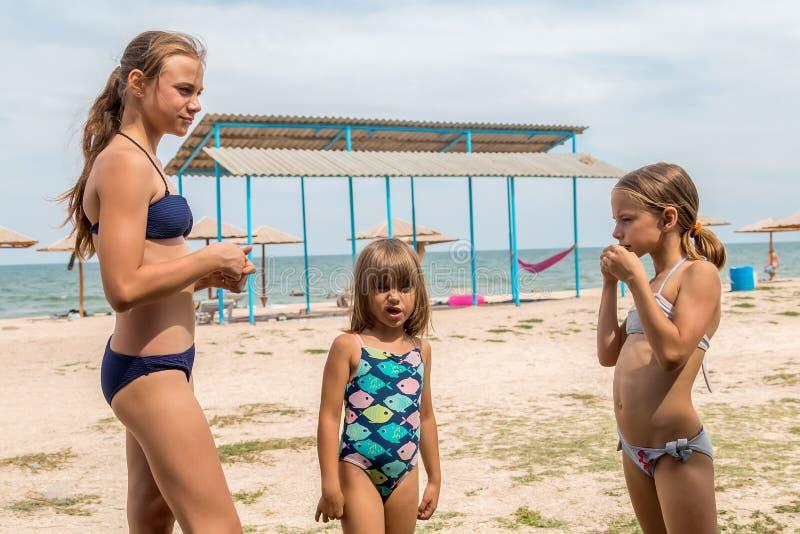 海滩的三个姐妹在沐浴比基尼泳装 库存图片