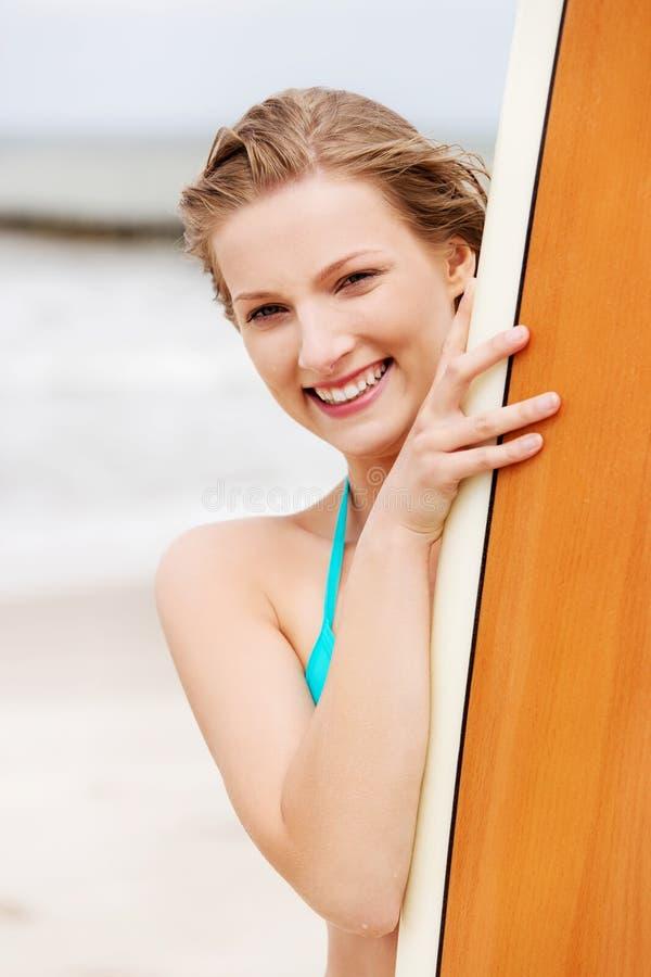 海滩的冲浪者女孩在比基尼泳装 免版税库存照片