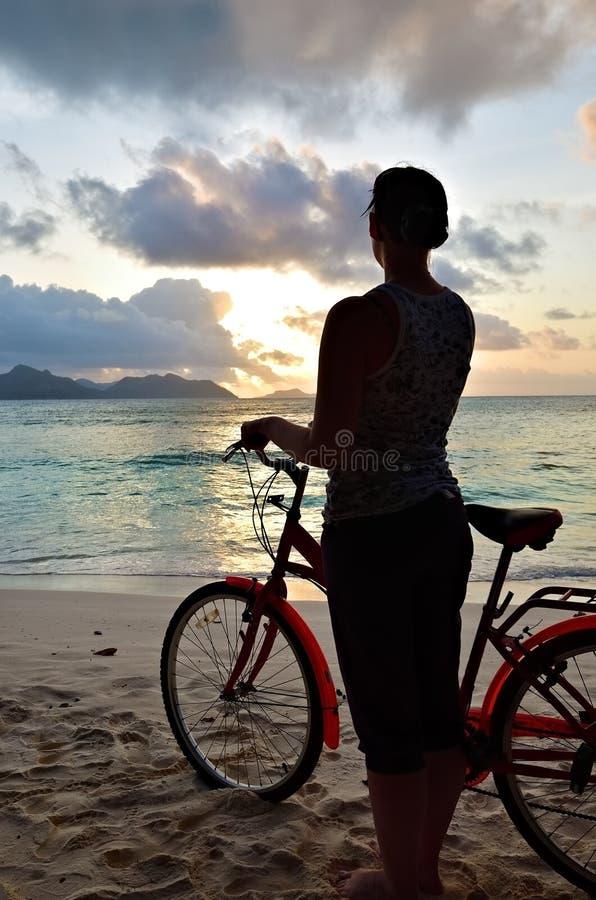 海滩的反对日落,塞舌尔群岛运动的女孩 免版税库存图片