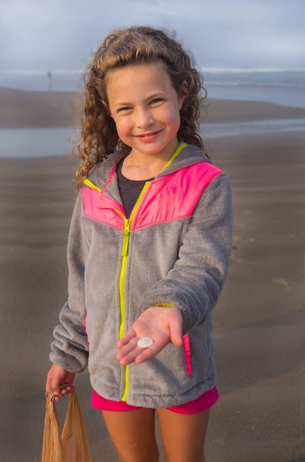 海滩的女孩与海壳垂直 免版税图库摄影