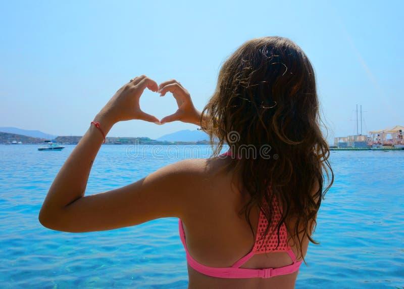 海滩的女孩,以心脏的形式手 免版税库存图片