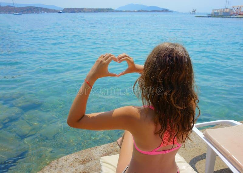 海滩的女孩,以心脏的形式手 库存照片