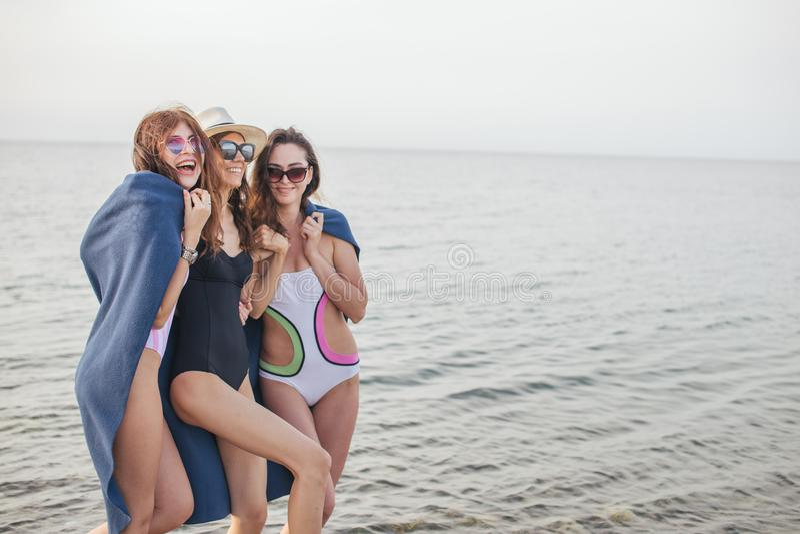 海滩的妇女与在平衡以后,暑假,假日,旅行的格子花呢披肩 图库摄影