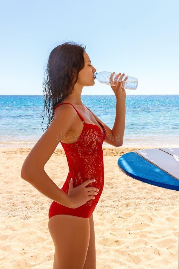 海滩的妇女喝在瓶的冷水 红色比基尼泳装的女性享受冰水饮料微笑的愉快笑的 库存照片