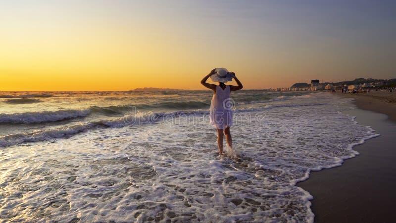 海滩的妇女在日落享受平静的海洋自然的在旅行假日期间 库存照片