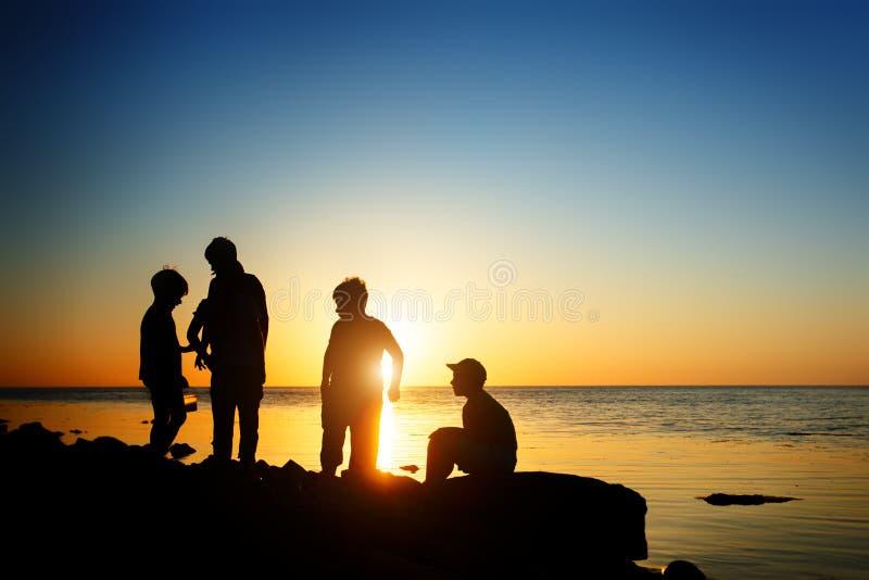 海滩的孩子,钓鱼 日落射击,背面图 背景峡湾光芒海运星期日 免版税库存照片
