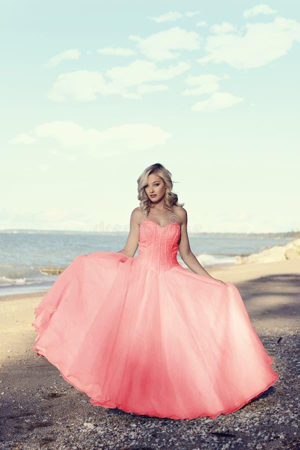 海滩的年轻白肤金发的妇女与红色薄纱舞会礼服 图库摄影