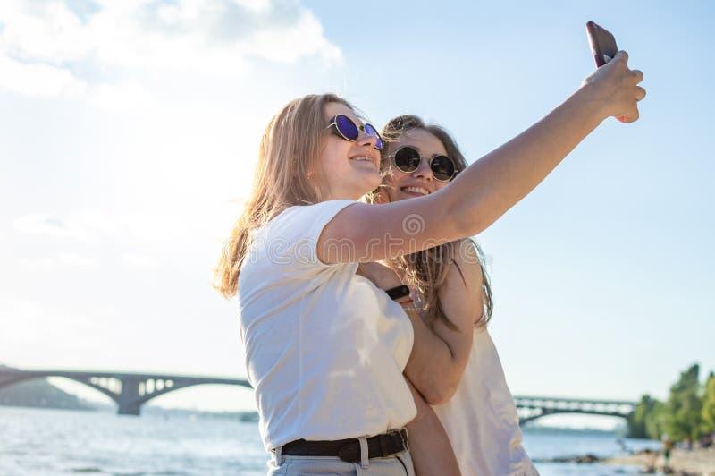 海滩的年轻美女,使用智能手机,他们采取在海的背景的一selfie 库存图片