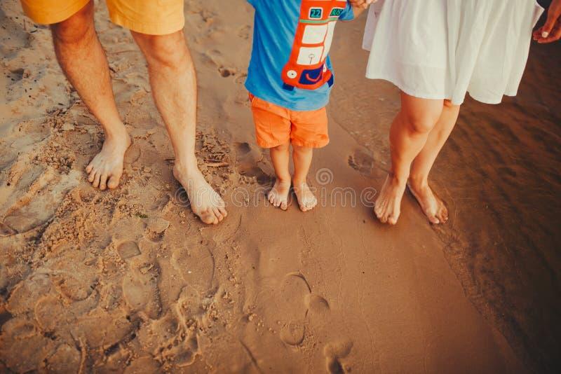 海滩的幸福家庭 家庭脚特写镜头与走在沙子的男孩婴孩的 抱着他们的婴孩的男人和妇女 由的步行 图库摄影