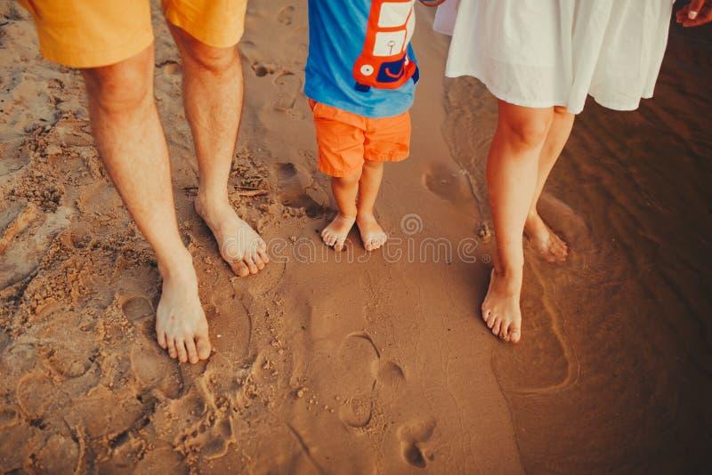 海滩的幸福家庭 家庭脚特写镜头与走在沙子的男孩婴孩的 抱着他们的婴孩的男人和妇女 由的步行 库存照片