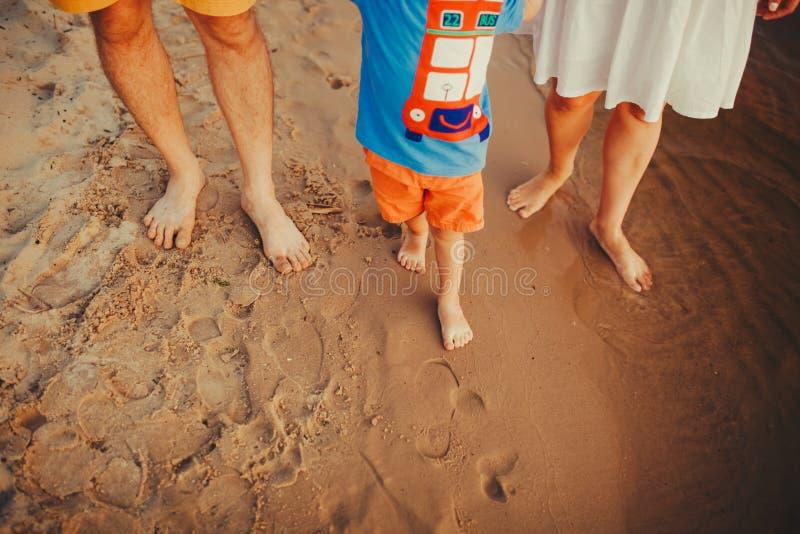 海滩的幸福家庭 家庭脚特写镜头与走在沙子的男孩婴孩的 抱着他们的婴孩的男人和妇女 由的步行 免版税库存图片
