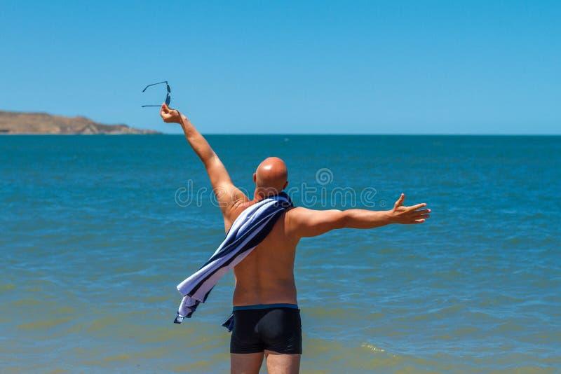 海滩的愉快的人享受休息和假期的概念的自由 免版税库存图片