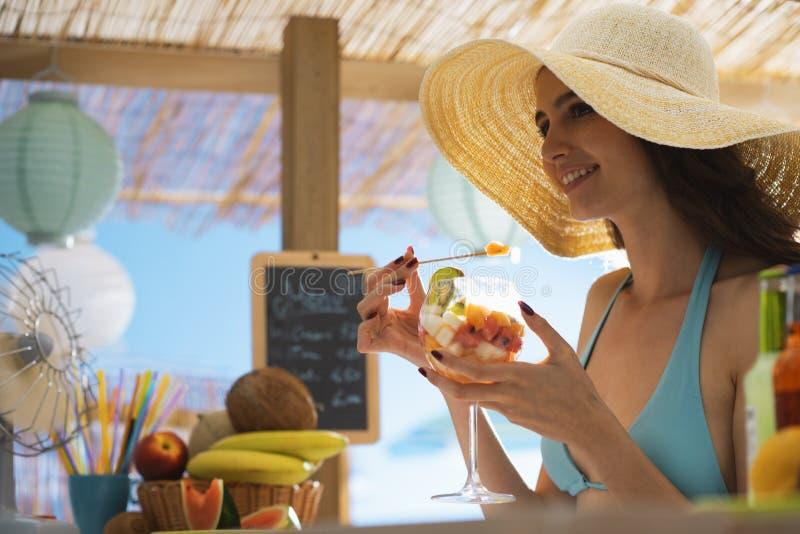 海滩的愉快的妇女吃水果沙拉的 免版税库存图片
