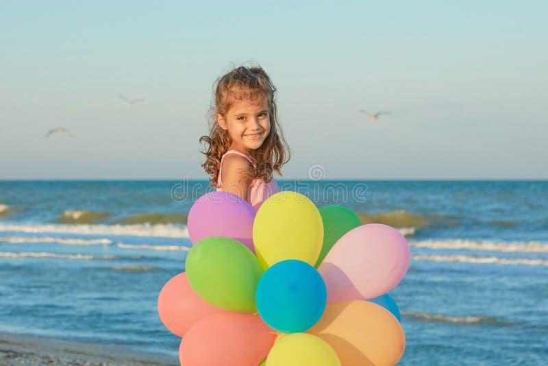 海滩的愉快的小女孩与气球 免版税库存图片